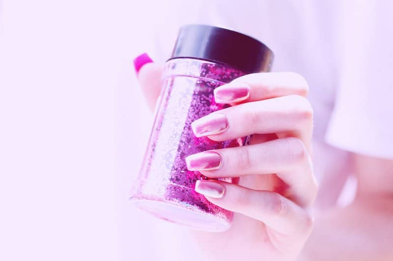 Close up of shiny hot pink acrylic nails and a bottle of magenta glitter.